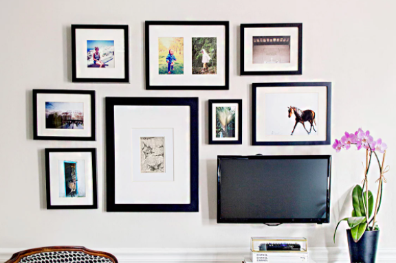 wall filled wih large square frames around tv
