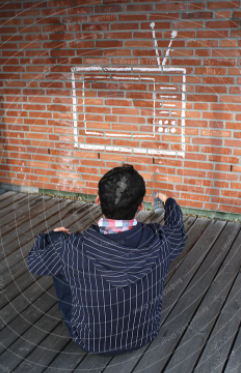 man sitting facing brick wall with TV drawn on in white chalk