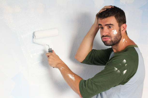 Stressed out male painting his home with space for copy.